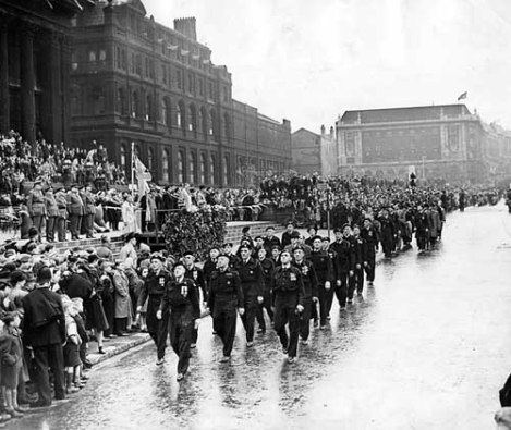 Victory Parade, marching past Leeds Town Hall is a contingent of Air Raid Wardens, the Lord Mayor Charles Walker is taking the salute.