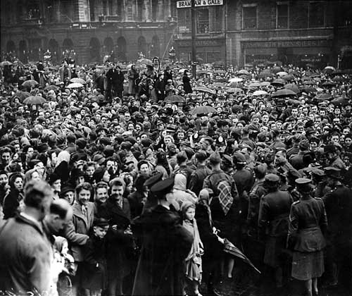 Dense crowds on The Headrow and Victoria Square, in front of Leeds Town Hall. They are waiting for the Victory Parade to begin, part of the VE celebrations.