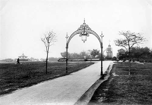 View down ornamental archways at Woodhouse Moor. A drinking fountain donated by Alderman North can be seen. 1897