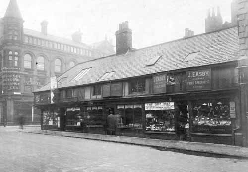14th September 1927. On left, offices of Liverpool Victoria Insurance Offices then the junction with Albion Street. No 24 George Eastman tobacconist. No 22 Alfred Warwick violin maker. No 20 A Kirk Verity antique dealers, double fronted shop. No 18 J Easby, left window is chocolates with notice declaring fire damage to factory. Right window displays fruit. These shops were estimated to be around 200 years old. Burley Bar was situated here, the westward limit of the ancient Leeds boundary. These shops were to be demolished for improvements to what was to be called the Headrow. Text and image taken from Leodis