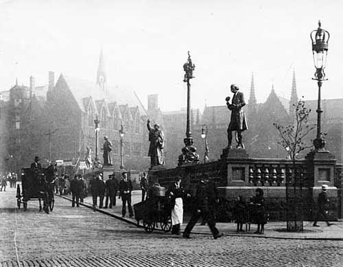 Undated. An early view of City Square with the spires of Mill Hill Chapel beyond on the right. City Square was designed to commemorate Leeds receiving city status in 1893 and the statues seen here were chosen to celebrate this. From the far left, James Watt (1736-1819) by Henry Charles Fehr for his effect on the industry by his improvements to the steam engine. Second from left, John Harrison also by Henry Charles Fehr, an influential figure in seventeenth century Leeds, endowed St John's Church. Walter Farquhar Hook, by Frederick Pomeroy, known as 'The Great Vicar of Leeds' and right Joseph Priestley by Alfred Drury, discoverer of oxygen. Taken from www.leodis.net