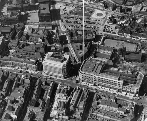 Aerial view of the city centre looking north, taken around the late 1950s. The Headrow is seen running from left to right, with Woodhouse Lane leading up from it. A car park can be seen at the top of the picture on the site which is now the Merrion Centre. At top-left are Thoresby High School (girls) and Leeds Central High School (boys) on Great George Street, with a playground in between, which amalgamated in 1972 to become City of Leeds School. (Image from www.leodis.net)