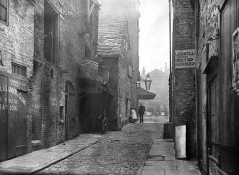 c.1887 View of the Rose and Crown Yard looking across Lands Lane to King Charles Croft. The larger of the two gas lamps is outside the Theatre Royal, the proprietor of the day was Jos. Hobson. The Rose and Crown Public House was a coaching inn, also known as 'Binks Hotel' after the landlady, Maria Binks. The Rose and Crown Yard was replaced by the Queen's arcade designed by architect, Edward Clark of London and opened in 1889. It linked Lands Lane with Briggate. From www.leodis.net