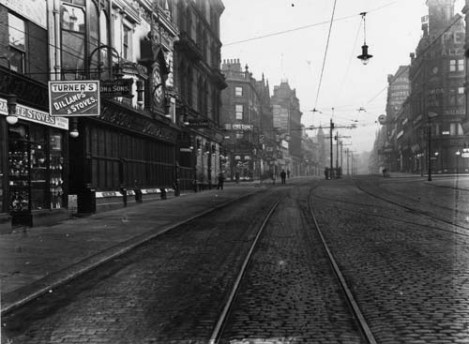 c1909. View of Briggate, looking north, and showing tram lines. Very few people are about so the photograph may have been taken very early in the morning. At the left edge is number 23 Briggate, Arthur R. Turner, Ironmonger, dealing in Oil Lamps and Stoves. Adjacent, at numbers 24, 25 and 26 is John Dyson & Sons, Watchmakers. Beyond Dyson's is the junction with Boar Lane. From www.leodis.net