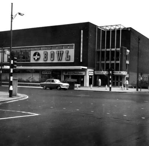 June 1967. View shows Arndale House and Carlines Supermarket. A lorry is unloading in the street. There are cars and a second lorry on the street.