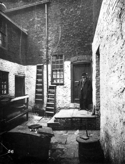 "1901. Small yard off Union Street, cluttered with various items, including ladders and a barrel. A man stands on the doorstep of a house, he is wearing a suit and bowler hat, and is probably a City Engineer. (Leeds Library and Information Service, <a href=""http://www.leodis.net/display.aspx?resourceIdentifier=2002109_55266970&DISPLAY=FULL"">www.leodis.net</a>)"