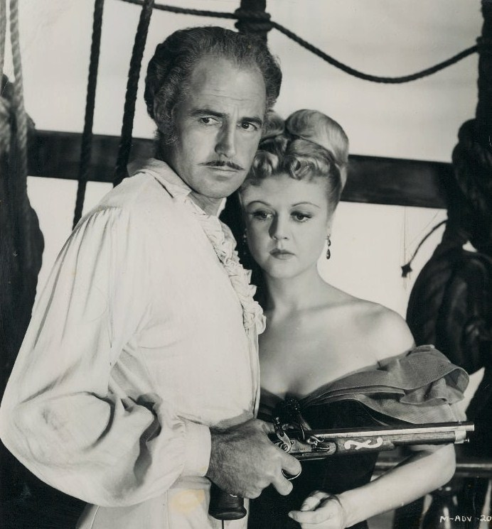 Image of Patric Knowles holding a revolver while grasping Angela Lansbury in a still from the 1952 film, Mutiny