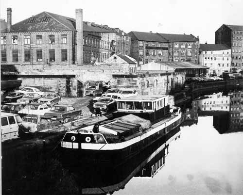 c1978. View from Leeds Bridge looking downstream, east, to former warehouses on the River Aire. From www.leodis.net, (c) Leeds Library and Information Service
