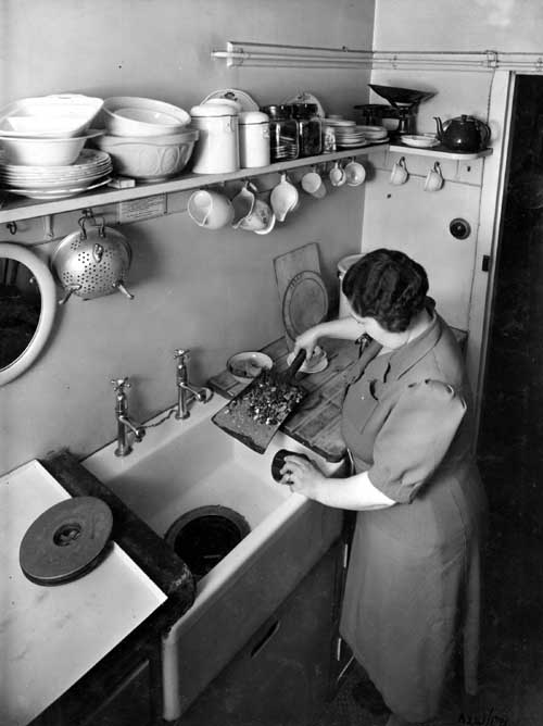 1943. Lady in kitchen demonstrating the use of the Garchey waste disposal unit in the sink (C) Leeds Libraries