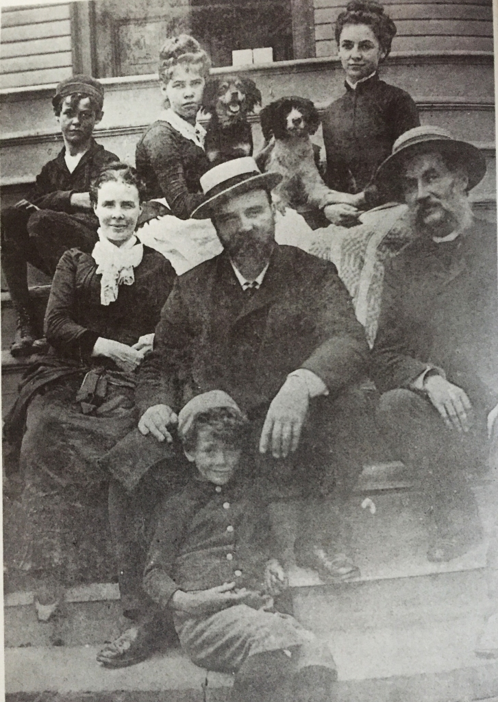Photograph of seven people, including two children, plus two dogs