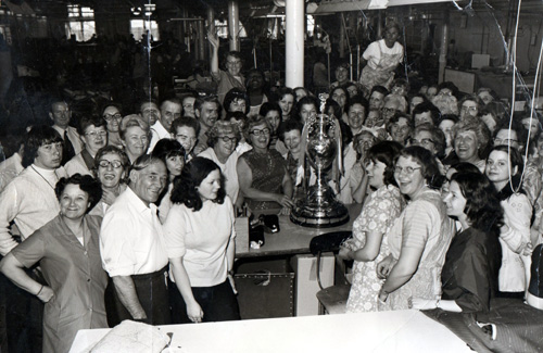 Crowd of people, mainly women, with football trophy