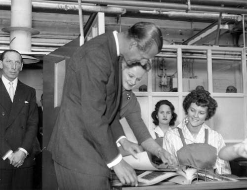 Prince Phillip talking to female workers at a factory